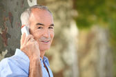 Grey haired man making telephone call in park — Stock Photo
