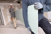 Workers carrying plasterboard — Stock Photo