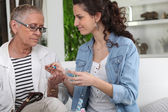 Helping grandmother with her medication — Stock Photo
