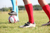 The feet of two football players on a field, one of them blocking a ball. — Stock Photo