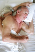 Older couple asleep in bed — Stock Photo