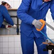 Stock Photo: Plumber sawing grey pipe