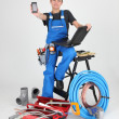 Woman plumber showing phone — Stock Photo #14095135