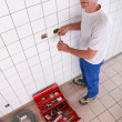 Stock Photo: Electricirepairing electrical outlet in bathroom