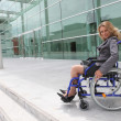 Stock Photo: Businesswomin wheelchair outside office block
