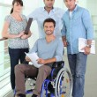 Smiling man in a wheelchair with colleagues — Stock Photo