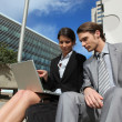 Smart couple with a laptop outside a corporate building — Stock Photo #14098997