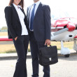 Stock Photo: Business couple standing in front of light aircraft