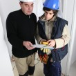 Stock Photo: Electriciwith young apprentice