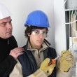 Stock Photo: Experienced electriciwatching his young apprentice