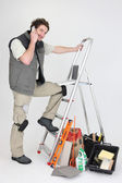 Workman making a call near ladder and miscellaneous tools — Stock Photo