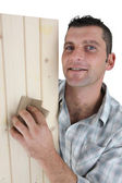 Carpenter sanding plank of wood — Stock Photo