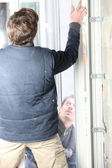 Two men fitting a new window — Foto de Stock