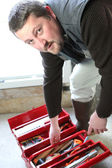Moonfaced craftsman bending over opened tool case — Stock Photo