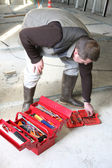 Worker looking for a tool in his toolbox — Stock Photo