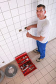 Electrician repairing electrical outlet in bathroom — Stock Photo