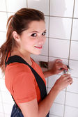 Female electrician working in a tiled room — Stock Photo