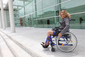 Businesswoman in wheelchair outside office block — Stock Photo