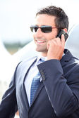 Businessman on a cellphone next to a light aircraft — Stock Photo