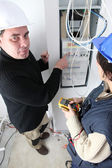 Electricians at a fusebox — Stock Photo
