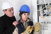 An experienced electrician watching his young apprentice — Stock Photo