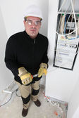 Electrician wiring a fusebox — Foto Stock