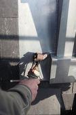 使用工具来熔化铅在窗口附近的体力劳动工人 — 图库照片