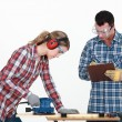 Man evaluating a tradeswoman on her use of a jigsaw — Stock Photo