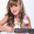 Fair-haired little girl playing bass - Stock Photo