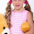 Little girl with huge teddy bear in arms — Stock Photo