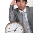 Business with clock suffering from headache - Foto Stock