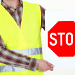 Highway worker with stop sign — Stok fotoğraf