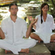 Stock Photo: Couple meditating in stone garden