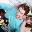 Couple sitting on a sofa with an electric guitar — Stock Photo
