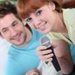 Couple singing and playing the guitar together — Stock Photo #14100871