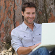 Stock Photo: Smiling man using laptop