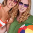 Two teenage girls wearing sunglasses and holding beach ball — Stock Photo