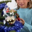 Boy decorating a Christmas tree — Stockfoto