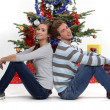 Young couple sat by Christmas tree — ストック写真