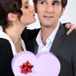 Woman kissing man with gift — Stock Photo