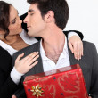 Couple with Christmas present about to kiss — Stock Photo