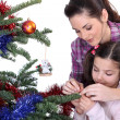 Mom and daughter decorating the Christmas tree — Stock Photo #14102140