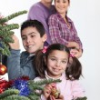 Happy parents with children decorating Christmas tree — ストック写真
