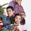 Happy parents with children decorating Christmas tree — 图库照片
