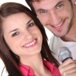 Stock Photo: Couple singing into microphone