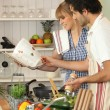Couple preparing a meal with the help of a cookbook - Stock Photo