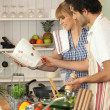 Couple preparing meal with help of cookbook — Stock Photo #14107700