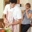Husband cooking whilst wife telephones — Stock Photo