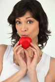 Attractive woman holding a small red heart — Stock Photo