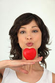 Woman kissing a heart — Stock Photo